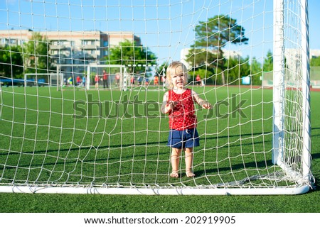 little girl baby blond / white hair resting on the grass / Outdoors. Little active football fan running on the green grass field with ball - stock photo