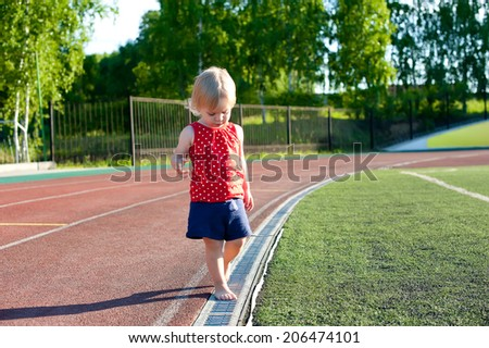 little girl baby blond / white hair resting on the grass / Outdoors. Little active football fan running on the green grass field - stock photo