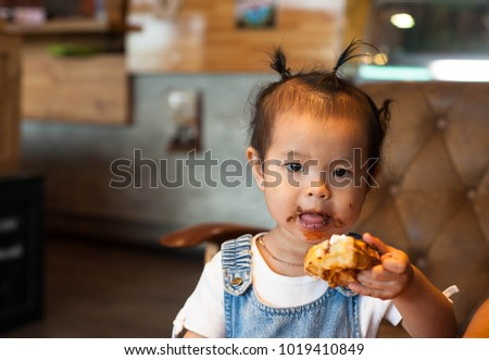 Little girl baby enjoy eating with her chocolate waffle in her hand at cake shop