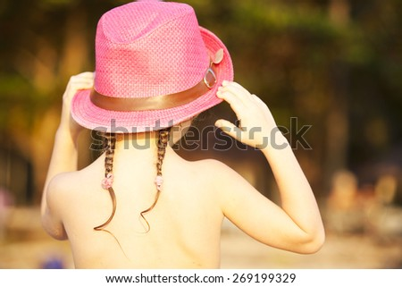 little girl back on the beach in a pink hat with braids - stock photo