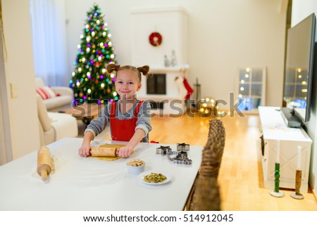 Little girl baking Christmas cookies at home