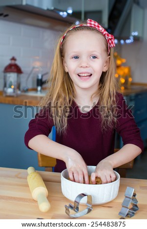 Little girl baking gingerbread cookies for Christmas at home kitchen - stock photo