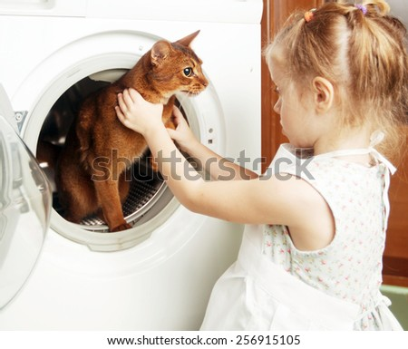little girl bathing the cat in the washing machine - stock photo