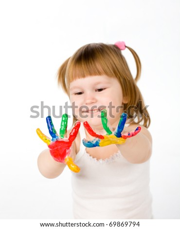 little girl bedaubed with bright colors. Small depth of sharpness. Focus on finger-tips.