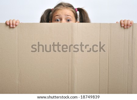 Little girl behind a blank cardboard (adequate for text), close up