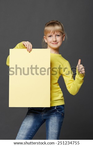 Little girl behind, holding blank advertising board banner, over black background - stock photo