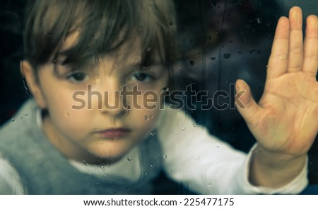 little girl behind window. rain drops on the glass. the girl wants to go playing outside but it s not possible because of the bad weather - stock photo