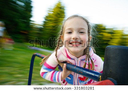 Little girl being happy, smiling on a moving merry-go-round with nature in the background. Healthy childhood concept.