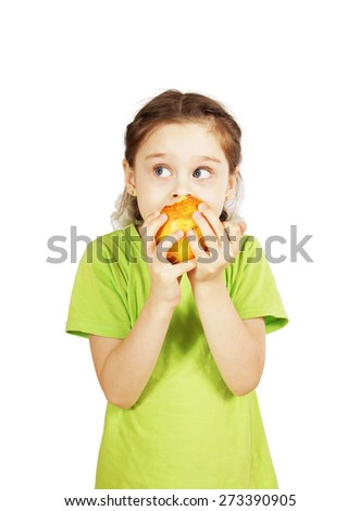 Little girl bites a big red apple and looks aside - stock photo