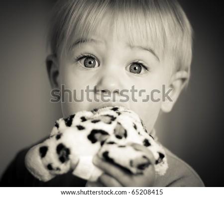 Little girl biting her stuffed leopard toy - stock photo