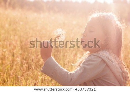 Little girl blowing away dandelion on meadow. Enjoying summer day.