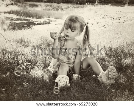 little girl blowing bubbles in sepia - stock photo