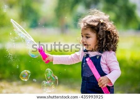 little girl blowing bubbles. Portrait of cute girl blowing soap bubbles. African-American girl blowing bubbles - stock photo