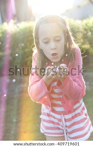 little girl blowing confetti  from her hands - stock photo