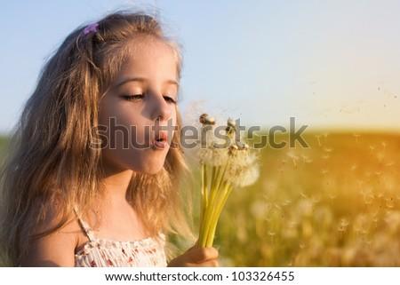 little girl blowing dandelion - stock photo