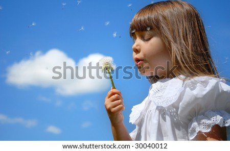 Little girl blowing dandelion, blue sky and heart shape cloud in the backgound - stock photo