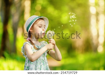 Little girl blowing dandelion in summer park - stock photo