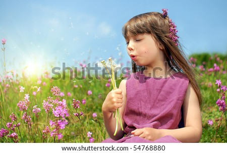 Little girl blowing dandelion on a hill full of beautiful flowers - stock photo