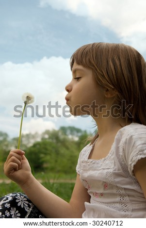 Little girl blowing dandelion on the meadow - stock photo