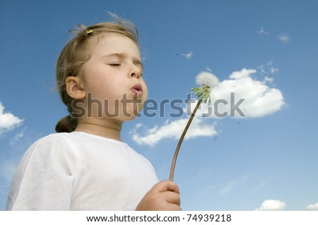 Little girl blowing dandelion - space for text - stock photo