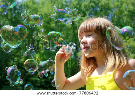Little girl blowing funny animals shaped soap bubbles