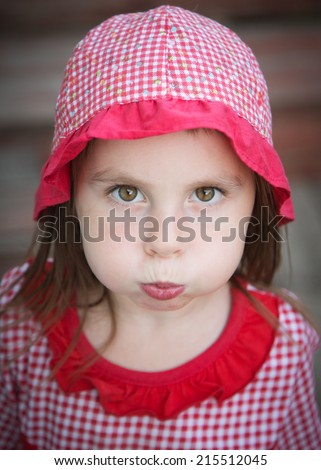 Little girl blowing her cheeks - stock photo