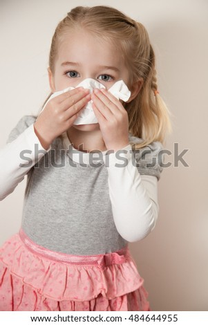 Little girl blowing her nose with a tissue