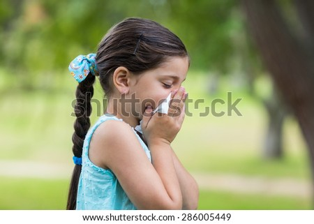 Little girl blowing his nose on a sunny day - stock photo
