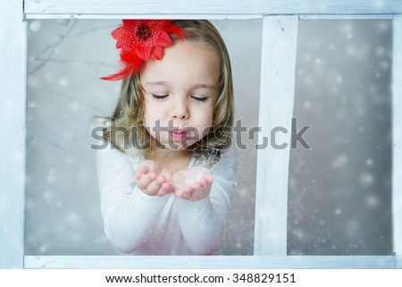 Little girl blowing snow - stock photo