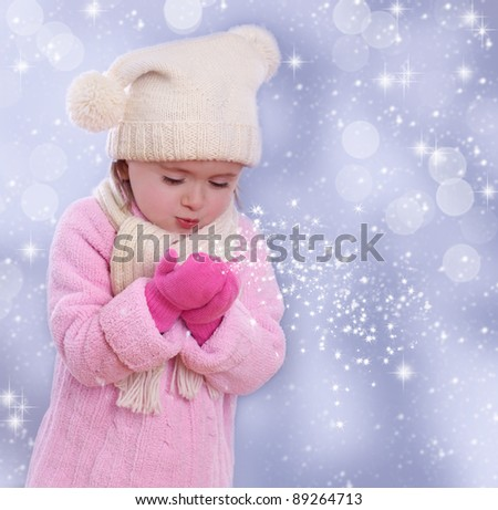 Little girl blowing snowflakes from her hands - stock photo