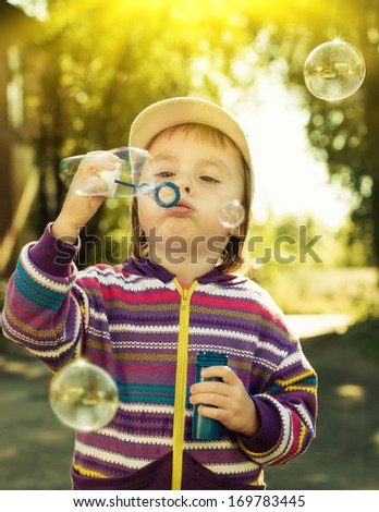 Little girl blowing soap bubbles. - stock photo