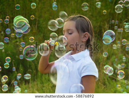 Little girl blowing soap bubbles at sunset - stock photo