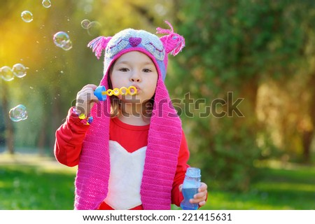 little girl blowing soap bubbles, closeup portrait.  - stock photo