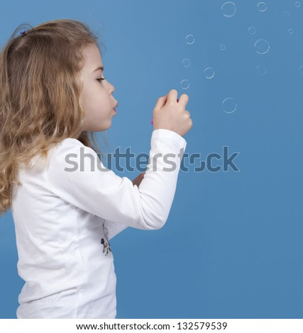 little girl blowing soap bubbles, isolated on blue background