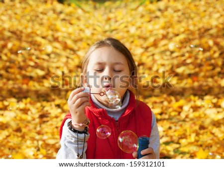 little girl blowing soap bubbles on a background of yellow foliage - stock photo