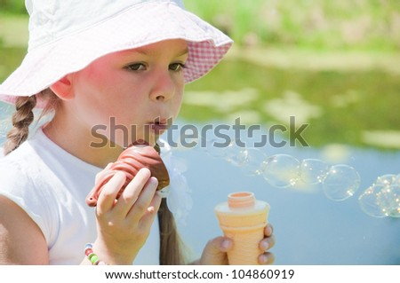 Little girl blowing soap bubbles outdoor - stock photo
