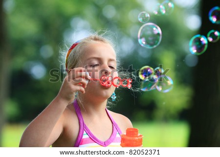 Little girl blowing soap bubbles outdoor