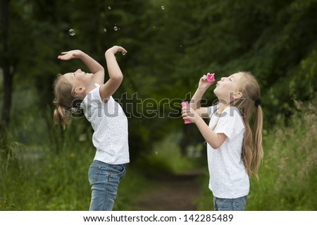 little girl blowing soap bubbles, outdoors - stock photo