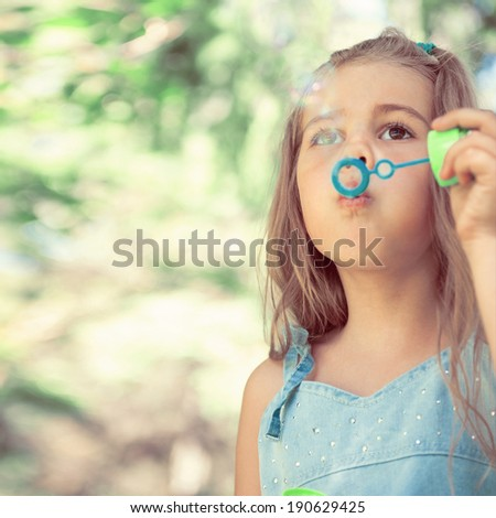 Little girl blowing soap bubbles outdoors at park. Retro style photo