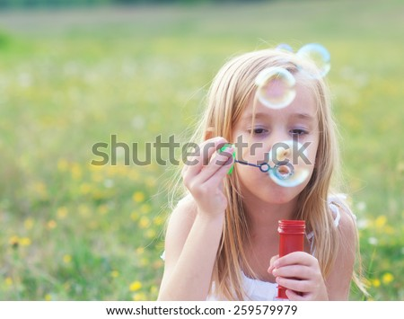 Little girl blowing soap bubbles while sitting in the meadow on beautiful spring day. - stock photo