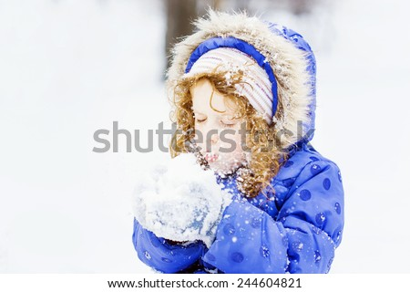 Little girl blows snow with mittens, on a snowflakes bokeh background . - stock photo