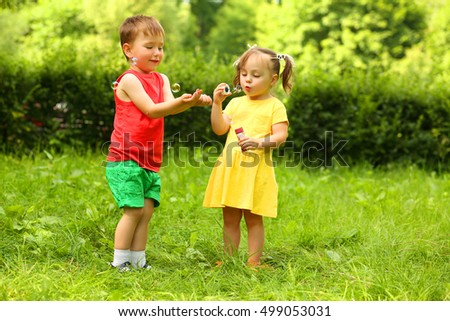 Little girl blows soap bubbles and boy plays with it on grass