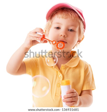 little girl blows soap bubbles over white background