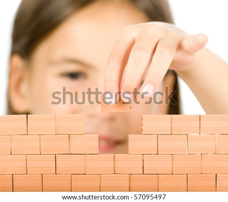 little girl building a wall - stock photo