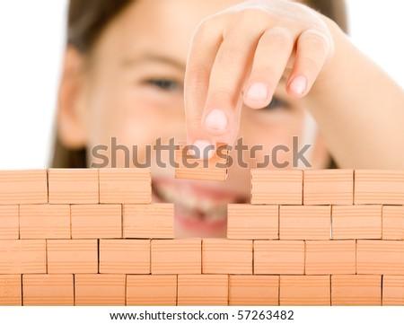 little girl building a wall focused on bricks - stock photo
