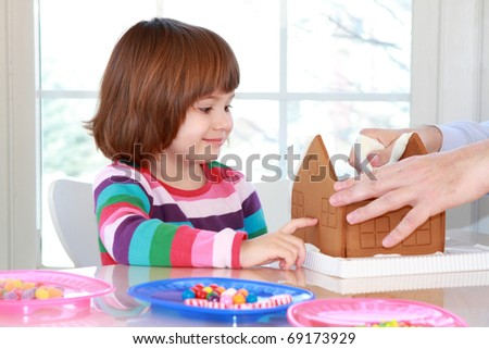 Little girl building and decorating gingerbread house with colorful candy for Christmas - stock photo
