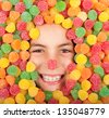 little girl buried on colored jellybeans - stock photo