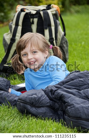 little girl camping laying on a sleeping bag - stock photo