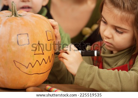 Little girl carving pumpkin for Halloween - stock photo