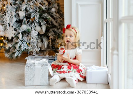 Little girl charming blonde, smiling and sitting on the floor against the backdrop of the Christmas tree in the interior of the house - stock photo